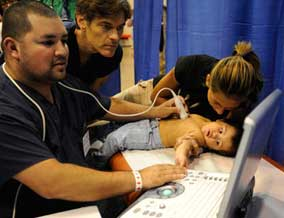 Dr. Oz treats a baby at the free clinic.
