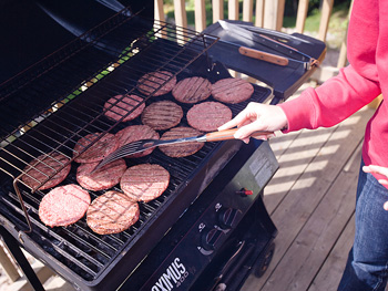 Woman barbecuing hamburgers