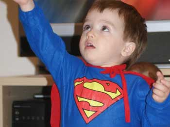 A little boy dressed as superman