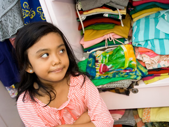Child in a closet full of clothes