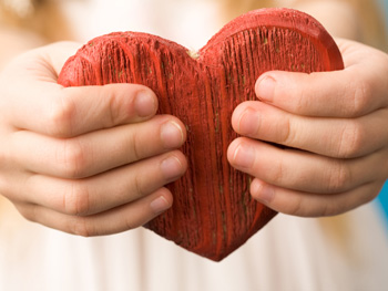 Child's hands holding a wooden heart