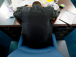 Man sleeping on messy desk