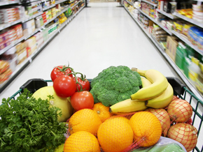 Grocery cart filled with organic vegetables in a supermarket