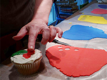 Decorating a cherry-themed cupcake