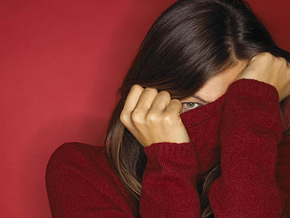 Woman hiding behind her sweater