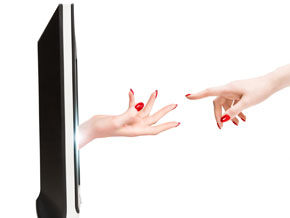A hand reaching out from a computer screen almost touching another hand