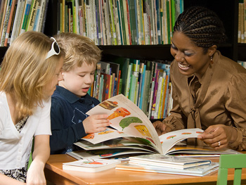 Woman helping children read