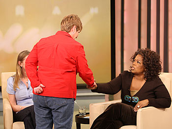 Oprah shakes hands with an audience member.