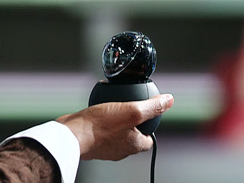 Oprah holds a webcam.