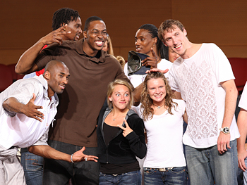 Olympic athletes, including members of the basketball and gymnastic teams, pose for pictures.