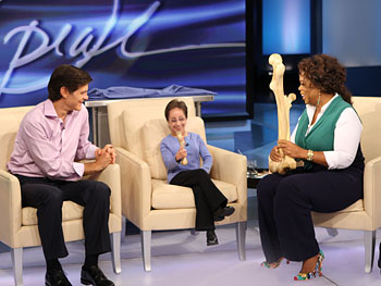 Dr. Oz show's Kristin a replica of her small femur, while Oprah holds a relica of Brenden's large femur.