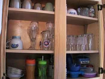 Organized glasses in a kitchen cabinet.