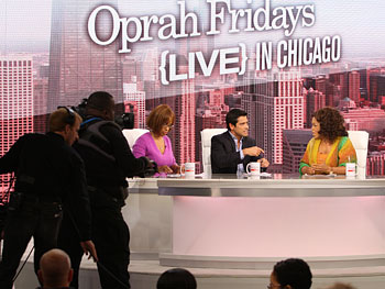 Cameramen move in for a better view of Gayle King, Mark Consuelos and Oprah.