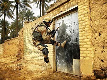 A soldier breaks down a door.