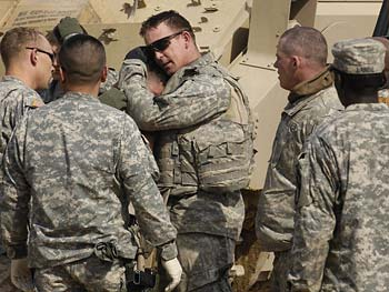 A soldier helps comfort his colleague.