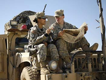Two soldiers talk over a newspaper.