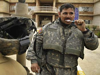 A soldier brushes his teeth.