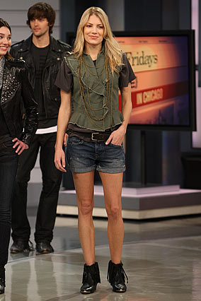 A woman models William Rast denim shorts, a New America flag silk T-shirt and a green biker vest.