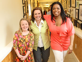 Emma Claire, Elizabeth and Oprah walk down a long hallway.