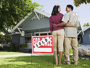 Couple in front of their first home sold