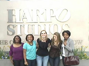Women gather in front of the Harpo Studios sign.