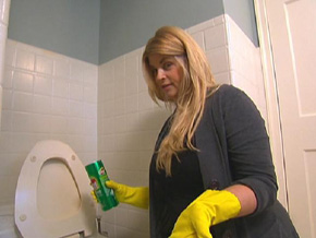 Kirstie Alley cleans a bathroom.